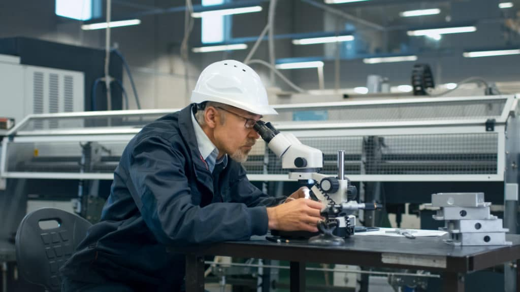 Senior engineer is inspecting a detail under microscope in a factory.