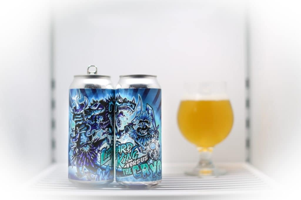 Two tall cans of Lizard King Versus the Cryo beer next to a glass of it, in a freezer